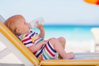 Portrait of baby on sunbed drinking water